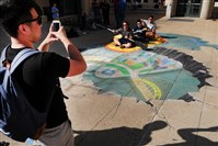 Carnegie Mellon student Kevin Louie takes a picture of fellow students Dan Kelley, Dale Zhang and Mahir Kothari interacting with a 3D chalk drawing on the sidewalk outside of the Carnegie Mellon University Center.