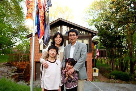 Tai Sing Lee, who grew up in Hong Kong, and his wife, Tomoko Nukui, who was raised in Japan, stand with children Harrison and Helen near their home in O'Hara. He studies the human visual system. She is a cancer researcher.