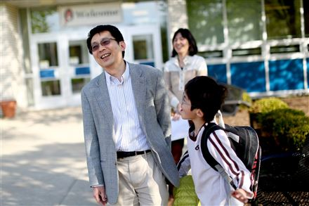 "Tai Sing Lee, a Carnegie Mellon University researcher and a new citizen, picks up his son, Harrison, from O'Hara Elementary School in O'Hara. ""I want my children to love America,"" said Mr. Lee, who typifies the highly educated Asian residents who have dominated Pittsburgh's recent immigration trends."