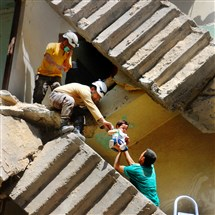 Syrian civil defense volunteers remove a baby from a destroyed building Thursday following a reported airstrike on the rebel-held neighborhood of al-Kalasa in the northern Syrian city of Aleppo.