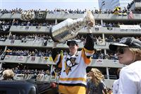 Sidney Crosby raises the Stanley Cup on the Boulevard of the Allies at the Pittsburgh Penguins' victory parade and rally.