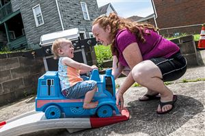 Karlee Brydges, 1, of Glassport, left, laughs as she is pushed by her mother Rebecca Brydges, of Glassport, right, while riding a toy train, Saturday, June 8, 2019, in Glassport. Issues with peeling paint and mold in their McKeesport home forced Rebecca Brydges to move her family to Glassport. Her kids now will attend the South Allegheny School District, which Ms. Brydges believes will better serve her son Jaxen, who is autistic. (Michael M. Santiago/Post-Gazette) #McKeesportCP